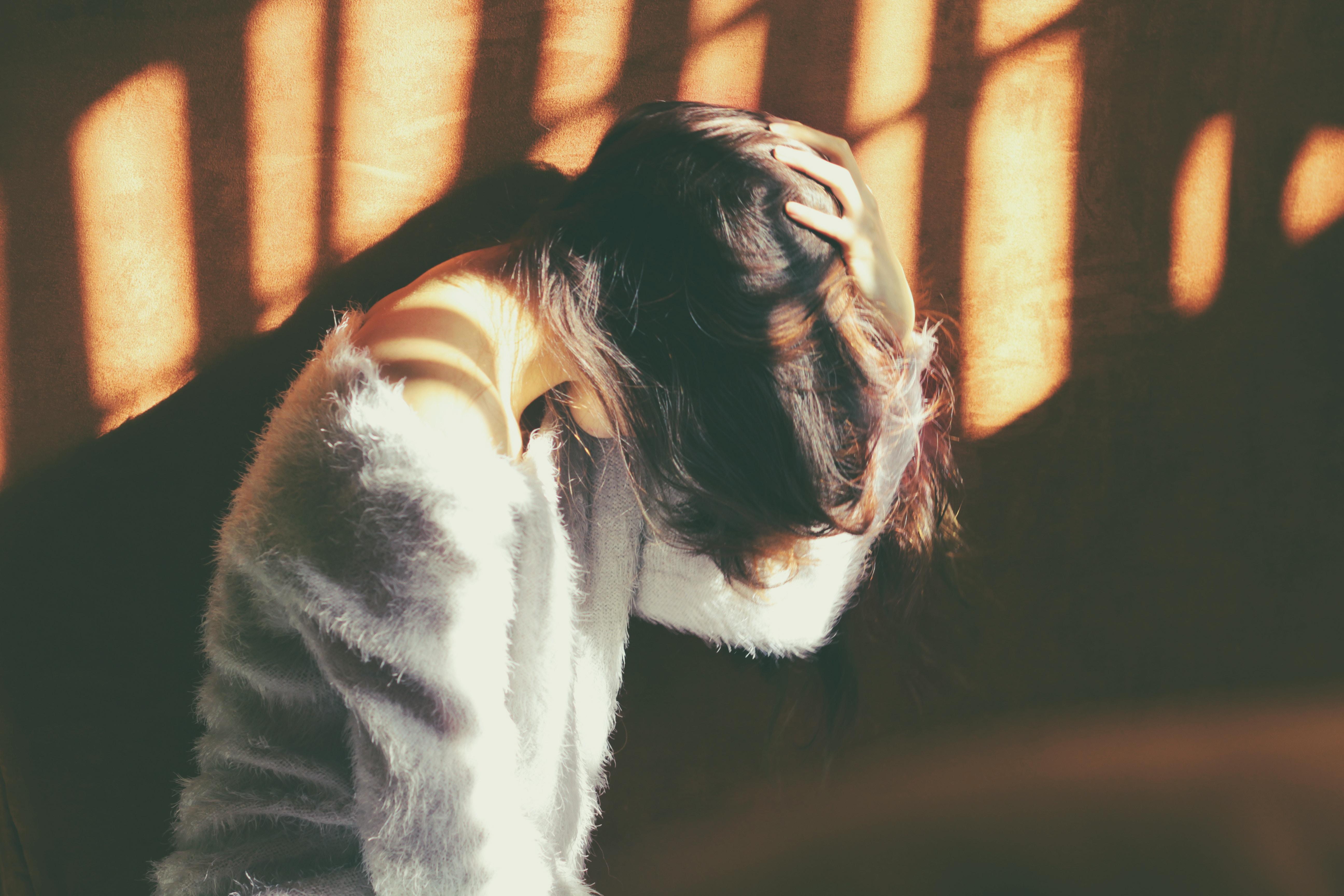 頭痛で頭を抱える女性の画像