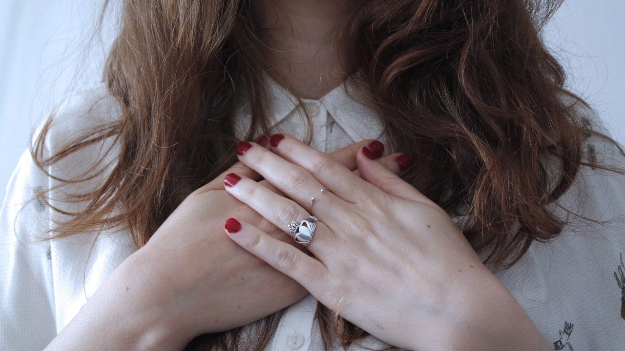 胸に手を当てる女性の画像